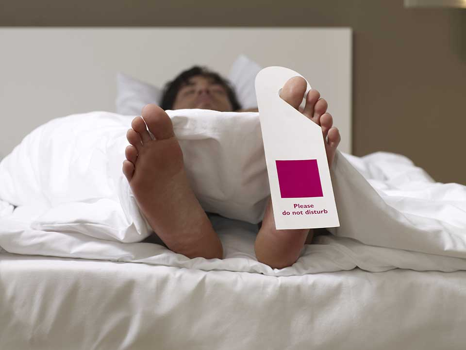 Man sleeping with 'do not disturb' sign on his toe.
